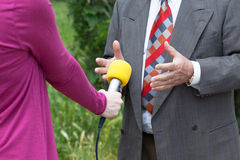 Media interview. Yellow microphone. Reporter making media interview with businessperson or politician Stock Images