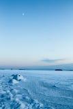 Media luna sobre el hielo marino sobre la hora del azul del invierno Imagen de archivo