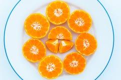 Media naranja de la fruta en una placa blanca. Fotografía de archivo