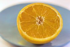Media naranja madura en una placa azul Imagen de archivo