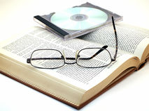 Media Overload. Glasses and CD in case lie on open leather-bound book Royalty Free Stock Photography