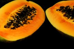 Media papaya en el fondo oscuro, cierre para arriba Imagenes de archivo