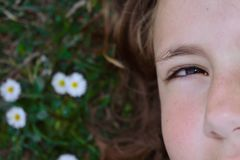 Media parte de la cara de una niña que se acuesta en la hierba fotografía de archivo