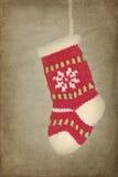 Media roja de Navidad que cuelga en fondo rústico Imágenes de archivo libres de regalías