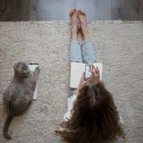 Media sociali di uso biondo sveglio su uno smartphone Sedendosi sul pavimento a casa con il gatto Vista dalla parte superiore Immagine Stock