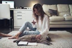 Media sociali di uso biondo sveglio su uno smartphone Sedendosi sul pavimento a casa e sulle coccole il gatto Fotografia Stock