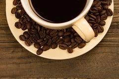 Media taza de café con las habas Fotos de archivo
