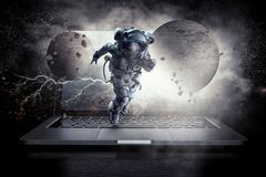 Media technology in space. Mixed media. Astronaut coming out of laptop screen. Mixed media Stock Images