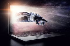 Media technology in space. Mixed media. Hand of astronaut coming out of laptop screen. Mixed media Royalty Free Stock Photography