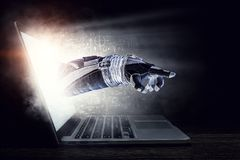 Media technology in space. Mixed media. Hand of astronaut coming out of laptop screen. Mixed media Stock Photo