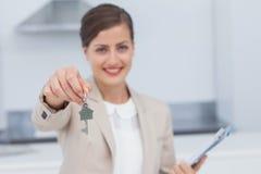 Mediador imobiliário bonito que dá a chave da casa fotografia de stock