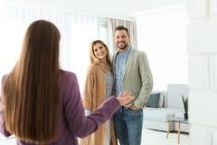 Mediador imobiliário fêmea que mostra a casa nova para acoplar-se fotografia de stock royalty free