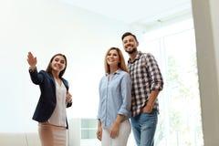 Mediador imobiliário fêmea que mostra a casa nova para acoplar-se imagem de stock