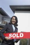 Mediador imobiliário Holding Sold Sign fora da casa Foto de Stock
