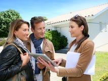 Mediador imobiliário que apresenta a casa nova aos clientes foto de stock