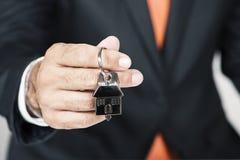 Mediador imobiliário que cede uma chave da casa Foto de Stock