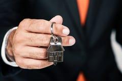 Mediador imobiliário que cede uma chave da casa Fotos de Stock Royalty Free