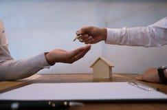 Mediador imobiliário que dá chaves ao cliente após o signatu do contrato Imagem de Stock Royalty Free
