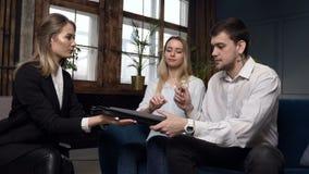 Mediador imobiliário que dá o contrato para a casa de compra, horizontalmente para que assinar acople-se dos clientes vídeos de arquivo