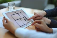 Mediador imobiliário que mostra planos da casa