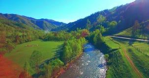 Mediados de aéreo sobre el río y el prado frescos de la montaña en la mañana soleada del verano Camino de tierra rural abajo almacen de metraje de vídeo