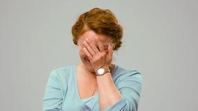 Mediados de actriz envejecida que muestra las emociones blandas, cubriendo su cara con la palma foto de archivo
