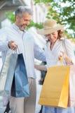 Mediados de compras adultas felices en el centro de ciudad, bolsos que hacen compras llenos que llevan de los pares foto de archivo
