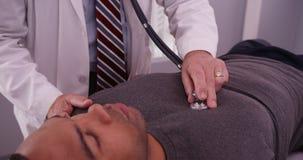Mediados de doctor envejecido que escucha los pulmones del paciente negro del varón adulto foto de archivo libre de regalías