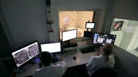 Mediados de enfermera adulta que prepara al paciente para la prueba de la exploración del CT en hospital almacen de video
