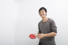 Mediados de hombre adulto hermoso que sostiene la paleta de los tenis de mesa Fotos de archivo libres de regalías