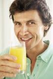Mediados de hombre adulto que bebe un vidrio de zumo de naranja Imagenes de archivo