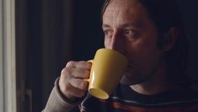 Mediados de hombre caucásico adulto que relaja y que bebe una taza de té, mirando fuera de ventana almacen de video