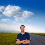 Mediados de hombre de la edad en camino en los prados que presentan los brazos cruzados Fotografía de archivo