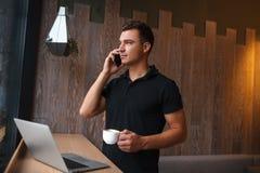 Mediados de hombre de negocios adulto que relaja y que bebe una taza de café Fotos de archivo libres de regalías