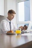 Mediados de hombre de negocios adulto usando el teléfono celular con el ordenador portátil en la mesa de desayuno Imagen de archivo libre de regalías