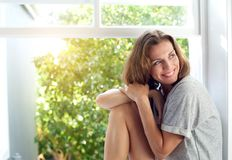 Mediados de mujer adulta feliz que se sienta por la ventana en casa Fotografía de archivo libre de regalías