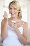 Mediados de mujer adulta que come el yogur Foto de archivo libre de regalías