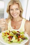 Mediados de mujer adulta que come una ensalada sana Fotografía de archivo libre de regalías