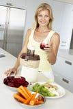 Mediados de mujer adulta que hace el jugo de las verduras frescas foto de archivo libre de regalías