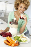 Mediados de mujer adulta que hace el jugo de las verduras frescas Fotografía de archivo