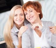 Mediados de mujer con la hija en cocina Foto de archivo libre de regalías