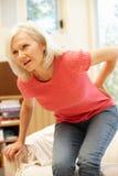 Mediados de mujer de la edad con dolor de espalda Fotos de archivo libres de regalías