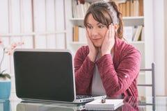 Mediados de mujer de la edad que se sienta en la tabla con el ordenador portátil fotos de archivo