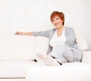 Mediados de mujer feliz en el sofá Imagen de archivo libre de regalías
