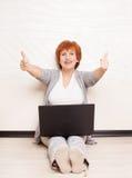 Mediados de mujer que se sienta en piso con el ordenador portátil Imagen de archivo libre de regalías