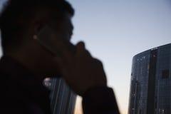Mediados de negocio adulto en el teléfono celular en la noche, silueta Imagen de archivo libre de regalías