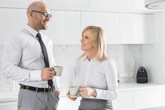 Mediados de pares adultos felices del negocio que comen café en cocina Imagen de archivo libre de regalías