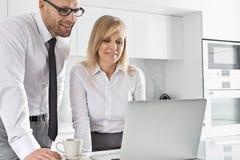 Mediados de pares adultos felices del negocio usando el ordenador portátil en la encimera Imágenes de archivo libres de regalías