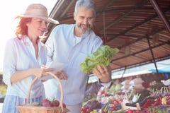 Mediados de pares adultos felices que compran verduras orgánicas frescas en un mercado foto de archivo libre de regalías