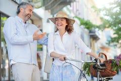 Mediados de pares adultos románticos que caminan a través del centro de ciudad fotos de archivo